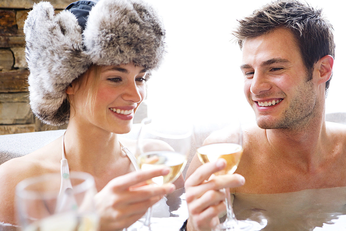 young couple après-ski champagne in hot tub